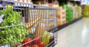 Shopping cart full of food in the supermarket aisle. Side tilt view. Horizontal composition